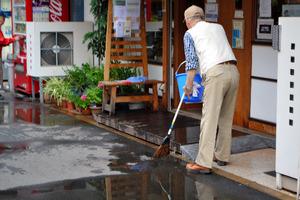 暮らしの保健室の前の道路を掃除す…