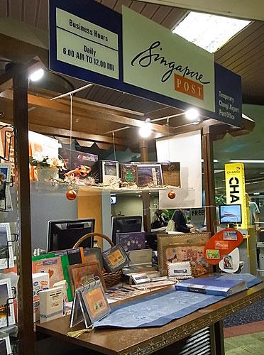 写真:簡易郵便局がいたるところにあります。ポストカードや記念切手なども選べます。後ろに見える「CHANGI」と書かれた黄色いライトがフリーインターネットブースの目印