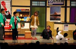 写真:吉本新喜劇の舞台に出演し、豪快にコケて見せた熊本県の蒲島郁夫知事(右から2人目)。知事の左はタレントのスザンヌさん=よしもとクリエイティブ・エージェンシー提供