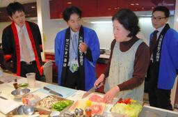 写真:法被姿の鹿児島県職員らに見守られながら、薩摩料理に挑戦する参加者=1月28日、大阪府豊中市、小河写す