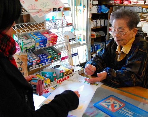 写真:切符を販売する江原米穀店の江原公子さん。食品などの商品と一緒に売っている=山陽小野田市