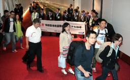 写真:新国際線旅客ターミナルがオープンし、初めて到着した乗客たち=21日午前5時51分、羽田空港、遠藤啓生撮影