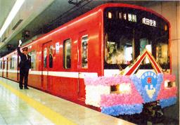 写真:1998年11月16日に乗り入れを果たした「羽田空港駅」から出発の合図を送る駅長=京急電鉄提供