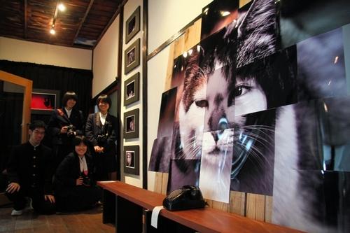 2階に展示された作品と下松高校美術部写真班の生徒たち=周南市土井2丁目の旧日下医院
