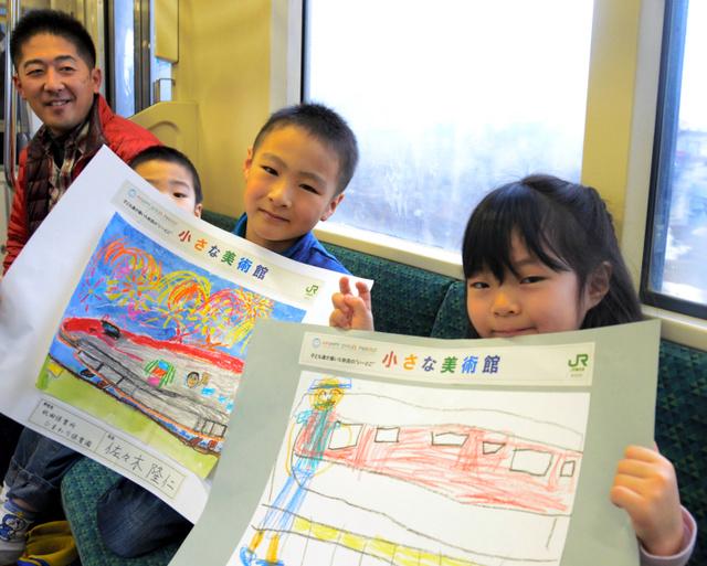 赤い車体の「スーパーこまち」を色鮮やかに描いた展示作を手に取るひまわり保育園の園児たち=JR奥羽線の臨時列車内