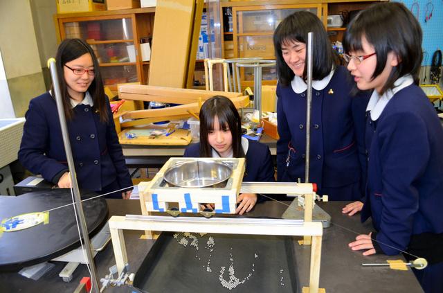 自作の装置でステンレス球の落下を実験するSSコースの女子生徒たち=彦根市金亀町の県立彦根東高校