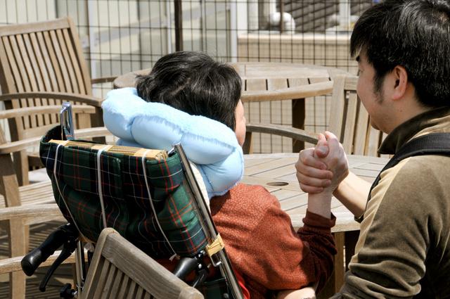 有料老人ホームの屋上で母の手を握りながら語りかける熊谷浩平さん(右)=東京都板橋区