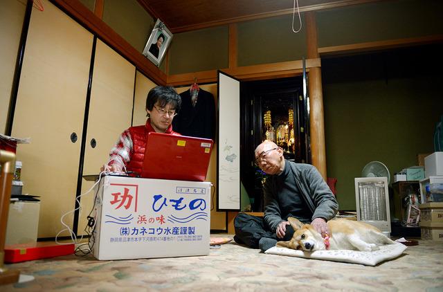 一人暮らしをする義父の義男さん(右)の自宅に定期的に通う新澤智生さん。突然の仕事に対応するため、パソコンは常に手放せないという=金沢市、小玉重隆撮影