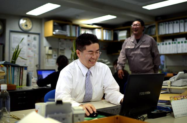 職場で仕事をする横澤昌典さん。介護はまだ続いているが、和やかな雰囲気で働けるという=横浜市、小玉重隆撮影