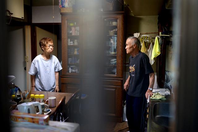 台所で川鍋健司さん(右)に食べ物を要求する妻の美津子さん。美津子さんの叫び声は外まで響いていた=東京都青梅市、小玉重隆撮影