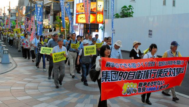 夕暮れ時の街を練り歩く「戦争をさせない奈良1000人委員会」のメンバーら=19日、奈良市