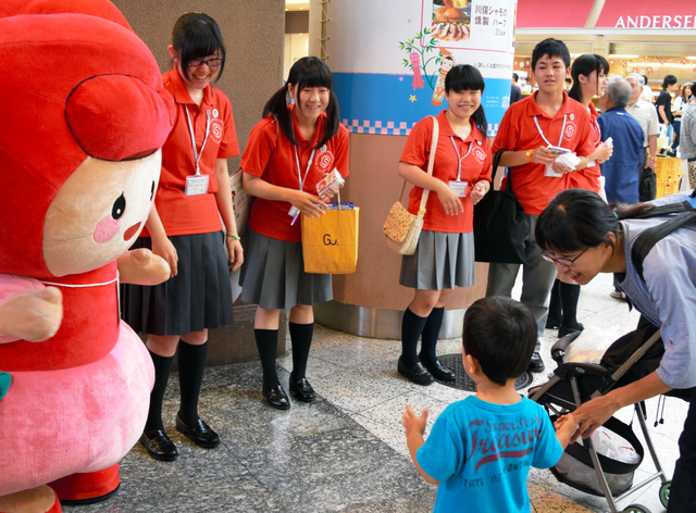 おそろいの赤シャツ姿でPR用のティッシュを配った=東京・上野駅