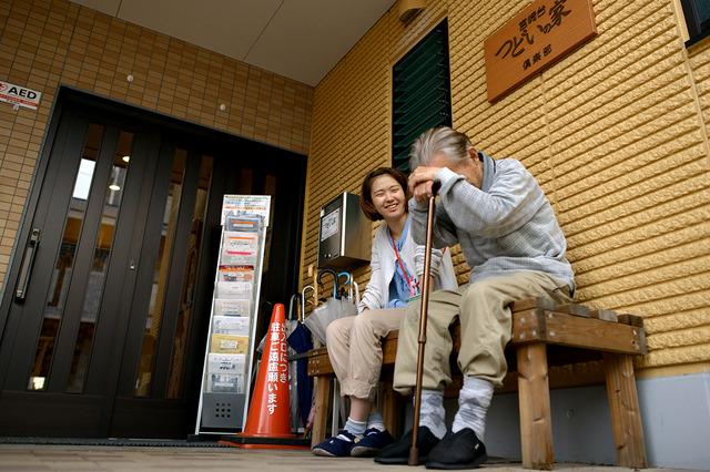玄関そばのベンチに座った男性(右)は、一休みして職員とおしゃべりを楽しんでいた=川崎市高津区、小玉重隆撮影