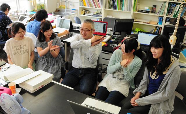 研究室ではやっているという「微生物のポーズ」を披露する粕谷健一教授(中央)と女子学生=桐生市天神町1丁目