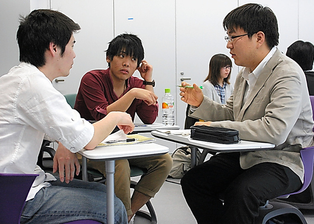 大学案内の長所や短所について、学生が小グループに分かれて話し合う=東京都豊島区の大正大