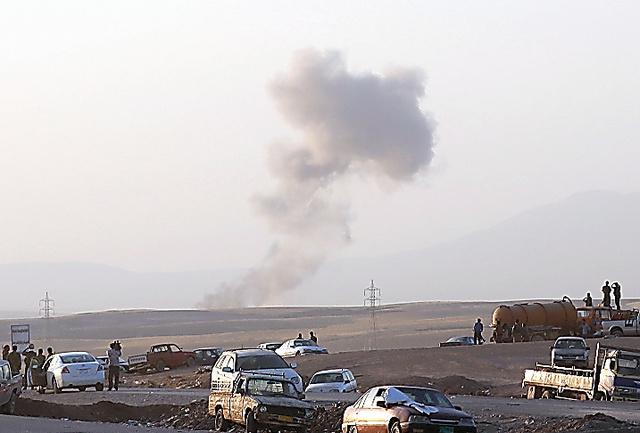 イラク北部のアルビル近くの検問所付近で8日、「イスラム国」に対する空爆が実施され、煙があがった=AP