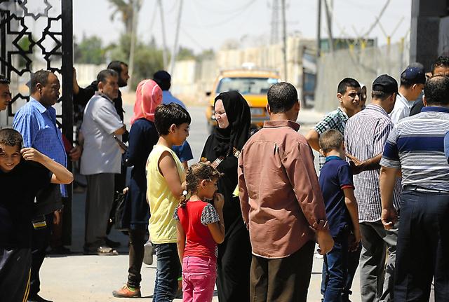 ガザ南部ラファの検問所の入り口で、エジプトの入国許可を待つ人たち