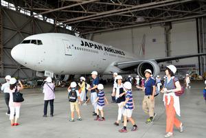 整備中の日本航空の旅客機を見学する親子連れら=日本航空の格納庫