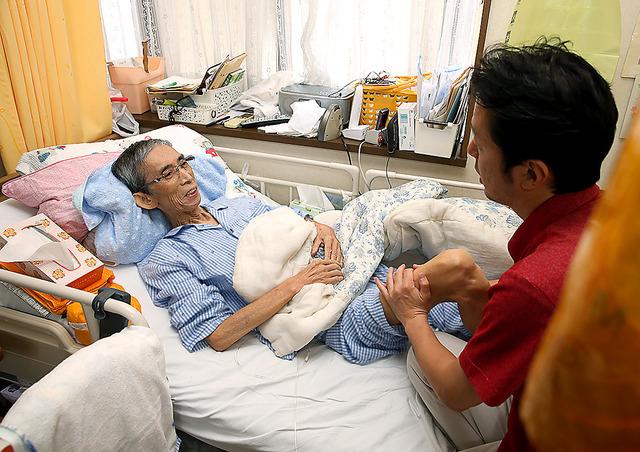 訪問看護師の広田芳和さんが足をマッサージ。田原松雄さんは「気持ちいいんだ」と笑った=横浜市瀬谷区、池永牧子撮影