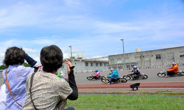 走路の間近でレースを観戦する産業観光ツアーの参加者=山陽小野田市の山陽オートレース場