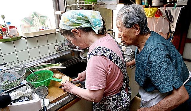 伊藤ケイ子さんと一緒に夕食の支度をする福永繁子さん(右)=大分県中津市、上田幸一撮影