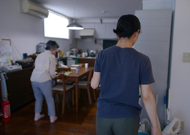 義母(左)の帰宅後、女性は夕食を出し、食卓を離れた=小玉重隆撮影