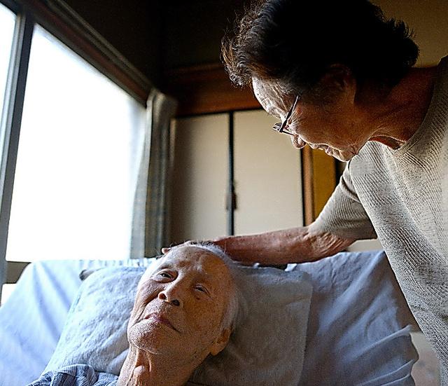 自宅で療養する辰夫さん(左)のそばに、いつも百合子さんが寄り添う=千葉県、小玉重隆撮影