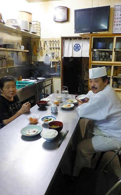 桑添正夫さんがいつも座っていた席(右手前)に陰膳をすえて食事をする家族=青森県三戸町