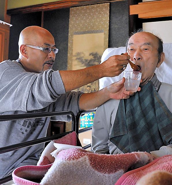 大久保晋さん(左)がスプーンで父、浩さんの口に手づくりの介護食を運ぶ。「最期まで好きな物を食べさせてあげたい」=岩手県遠野市