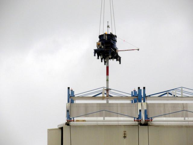 1号機建屋カバーで始まった作業。クレーンの先に付けた機械で穴を開け、飛散防止剤を注入する=22日午前7時7分、福島第一原発、東京電力提供