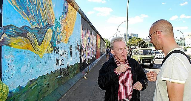 写真・図版 ベルリンの壁の前で、旧東独での体験を観光客に語って聞かせるドラウシュケ... (統一