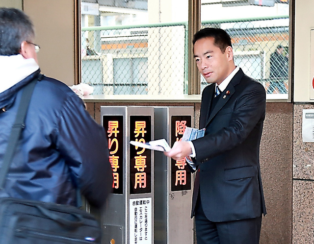 JR河辺駅前で通勤客らにパンフレットを手渡す井上信治衆院議員=東京都青梅市