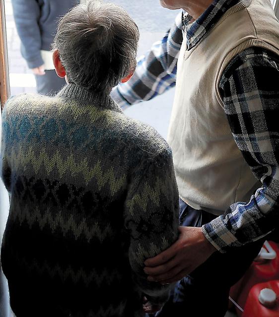 朝、母親の体を支えながら、デイサービスに送り出す男性。すぐに店へ出る