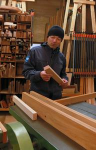 工作機械の前で木材を品定めする佐藤さん。一つの作業が終わる度に掃除と手入れをするため、機械はピカピカだ=東京都奥多摩町氷川