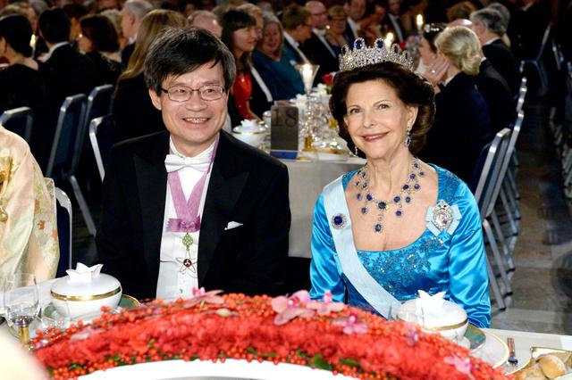 晩餐会にのぞむ天野浩・名古屋大教授(左)。右はスウェーデンのシルビア王妃=10日、ストックホルム市庁舎、ロイター