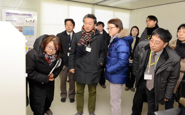 小名浜魚市場に設置された検査機をのぞき込む韓国の専門家委員会の委員ら=いわき市小名浜