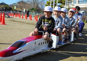 高校生が作ったミニ新幹線に乗車して喜ぶ牛島小の児童たち=春日部市牛島