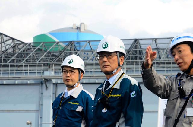川内原発の津波対策について説明を受ける田中俊一・原子力規制委員長(中央)。後ろは防護壁。奥は2号機原子炉建屋=鹿児島県薩摩川内市、小池寛木撮影