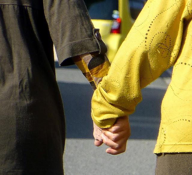 今回の連載では成年後見についてもとりあげた。写真は散歩に出かける認知症の女性(右)と、手をつなぐ後見人