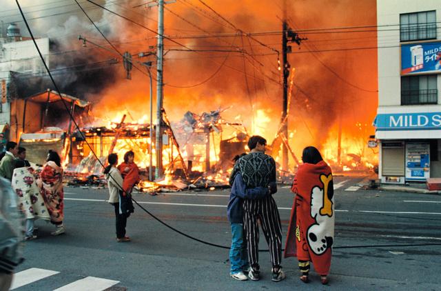 1995年1月17日の朝、赤い服を着た長男を抱き、燃える街を見る岡本祐佳里さん(右から5人目)=神戸市長田区、山崎直純撮影
