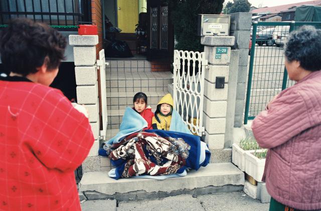 1995年1月17日、姉と寄り添って玄関前に座る武内唯史さん=西宮市鳴尾町5丁目、郭允撮影