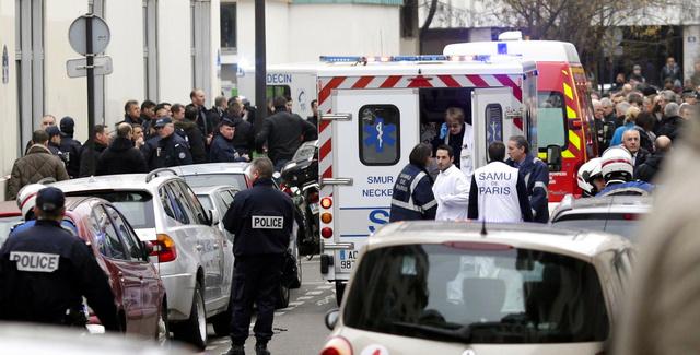 パリで7日、武装した男らによる襲撃を受けた週刊新聞「シャルリー・エブド」の事務所周辺に集まった大勢の警察官ら=AFP時事