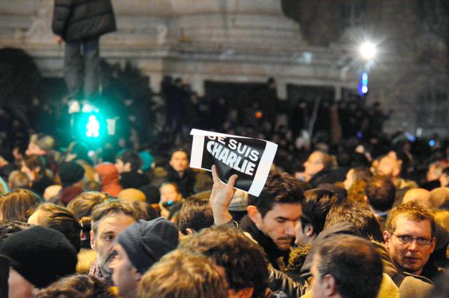 パリの週刊新聞「シャルリー・エブド」が襲撃された事件があった7日夕、犠牲者らを悼む集会で、「私はシャルリー」と記したカードを掲げる人も=パリ、吉田美智子撮影