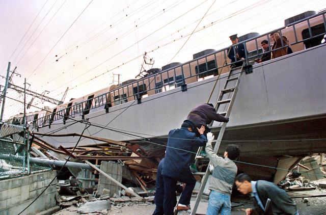 1995年1月17日、地震で高架橋が崩れ落ち、脱線して傾く阪神電車。山中勝さんは、はしごの上でロープを握り、乗客が下りるのを手伝った=神戸市灘区、小坂知博撮影