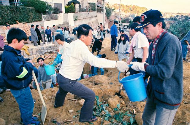 1995年1月17日、バケツリレーで土砂の下の炎を消しながら、埋まった人を捜す地域の住民たち=兵庫県西宮市、新井義顕撮影