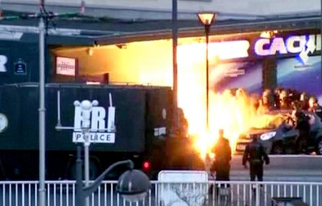 パリ東部のバンセンヌ地区で9日、仏特殊部隊の突入とともに、容疑者が立てこもったユダヤ系食材のスーパーマーケット正面で閃光(せんこう)が起きた=ロイター
