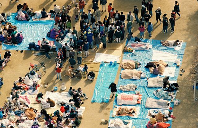 1995年1月17日、東灘小学校の校庭に避難し、シートの上に布団を敷いて暖を取る人たち=神戸市東灘区、本社ヘリから、森下東樹撮影