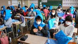 屋内退避訓練で着席してずきんをかぶる児童たち=東松島市大曲の大曲小学校