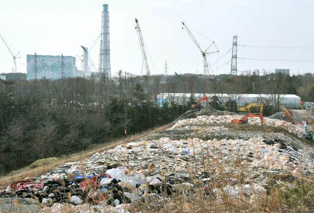 東京電力福島第一原発敷地内のがれき集積場。行き場の決まらない廃棄物が積まれていた。左後方は6号機=2月24日、福島県双葉町、仙波理撮影