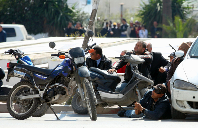 チュニジアの首都チュニスで18日、国会議事堂の外の道路に身を置く警察官。武装グループが博物館を襲撃し、観光客らを殺害した=ロイター